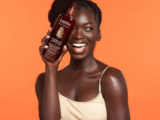 Campaign image of a black woman smiling in a light coloured top holding a bottle of product for Cantu Skincare range