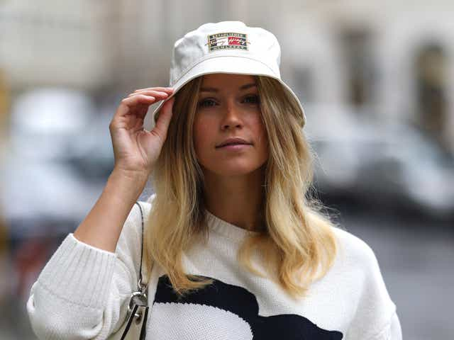 A street style model wears a white sweater and bucket hat.