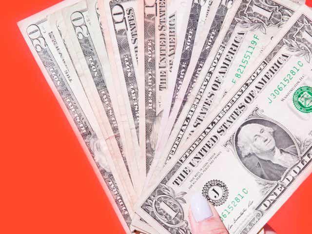 Dollar bills held up on an orange background.