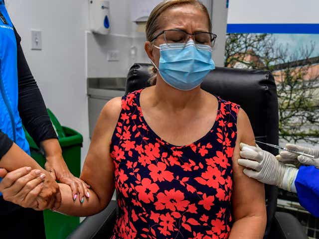 Woman wearing a red top and blue mask holds someone's hand before getting vaccinated.