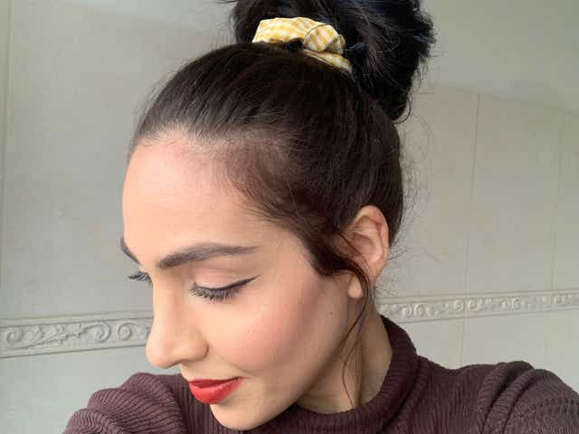 Jacqueline wearing a brown mock neck and red lipstick with a messy bun secured by a yellow gingham scrunchie