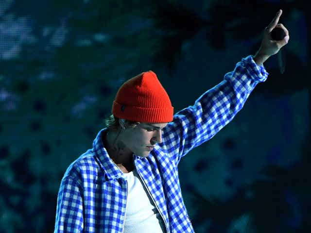 Justin Bieber in blue shirt and red hat holding his arm up.