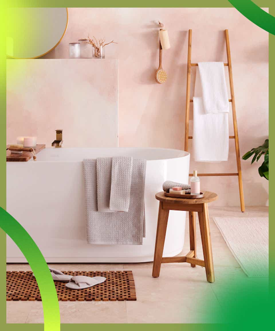 Bathtub with wooden bench and color-coordinated towels, salmon pink walls