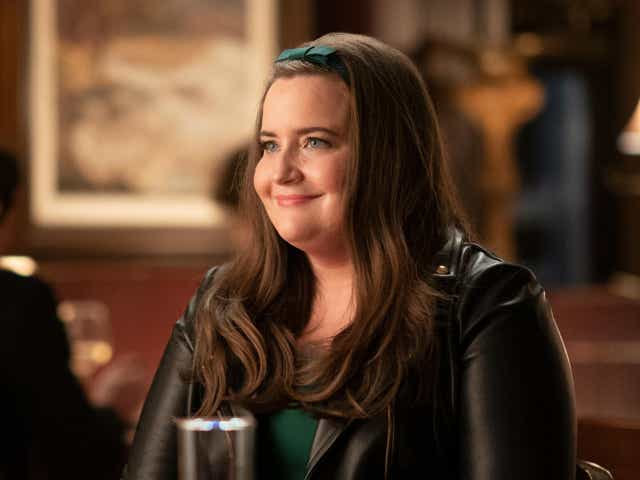 Aidy Bryant as Annie in Shrill. She's on a date, wearing a leather jacket and sitting at a table.