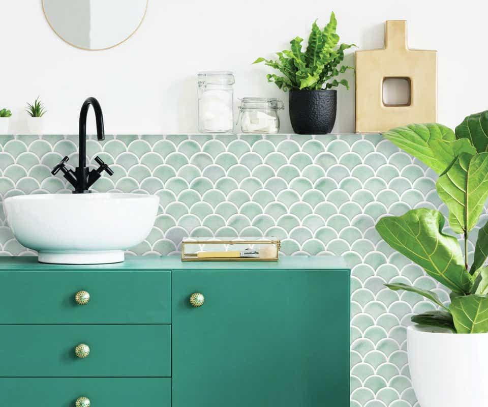 Mint green tile-print peel and stick tiles and green vanity, white sink.