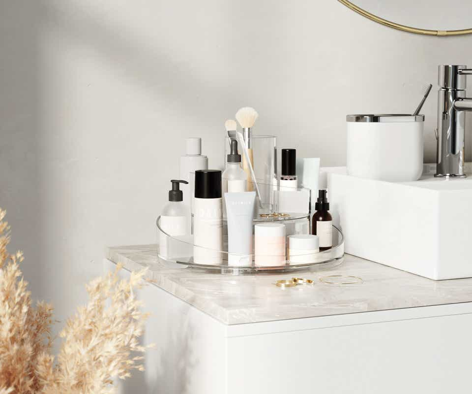 Round storage tray on sink with beauty products.