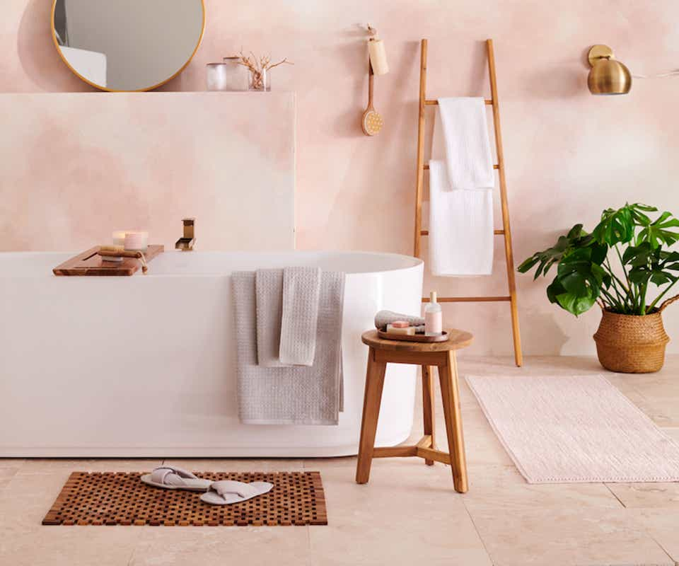 White bathtub, wooden stool, color-coordinated towels, salmon pink walls.