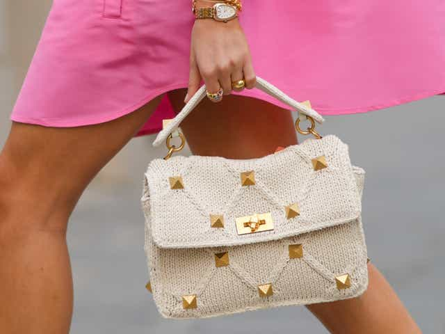 A street-style model wears a pink dress and carries a white top-handle purse with gold studs.