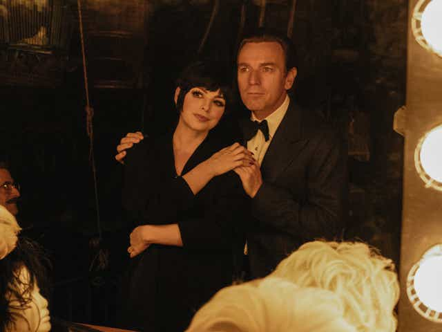 Krysta Rodriguez and Ewan McGregor embrace and look into a dressing room mirror together, as Liza Minelli and Roy Halston.