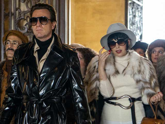 Ewan McGregor and Krysta Rodriguez as Halston and Liza Minelli in Halston. Ewan is wearing a patent leather trench coat and Liza is wearing white pants, white sweater, and a white fur shawl.