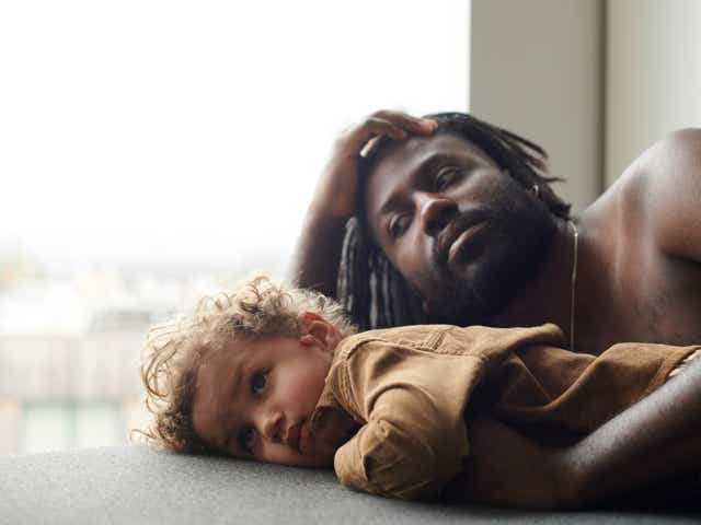 Father and child pose calmly by window