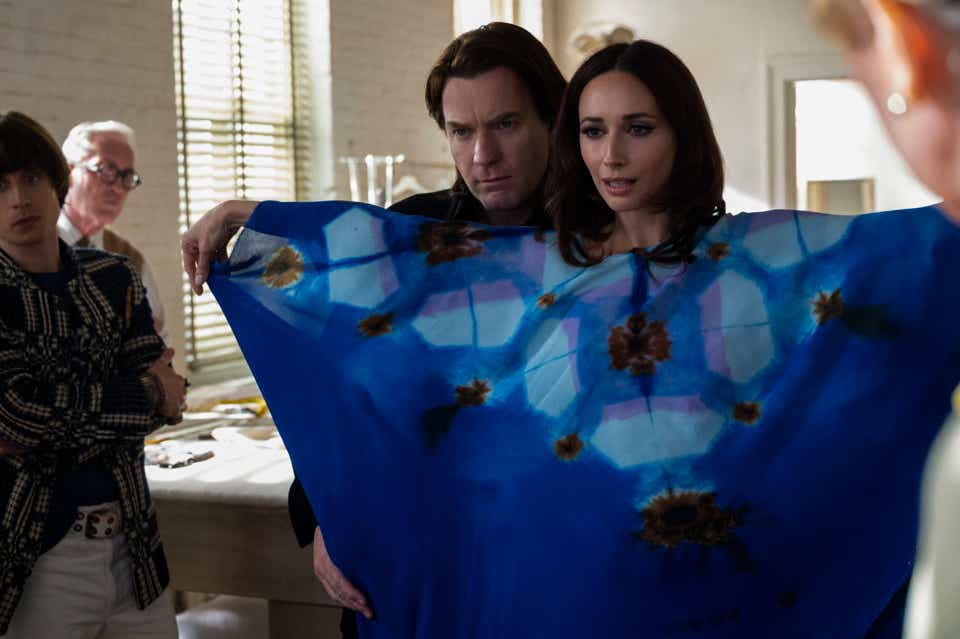 A still from Halston series showing Ewan McGregor as Halston and Rebecca Dayan in a tie-dye caftan as Elsa Peretti.