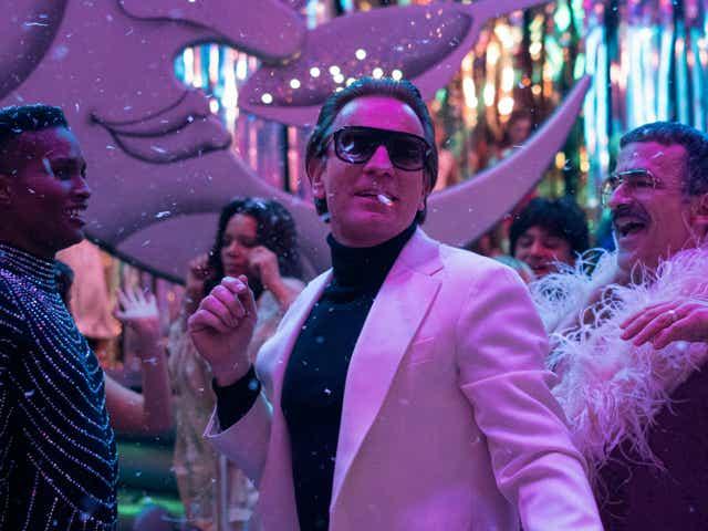 Ewan McGregor as Halston dances under purple light at Studio 54.