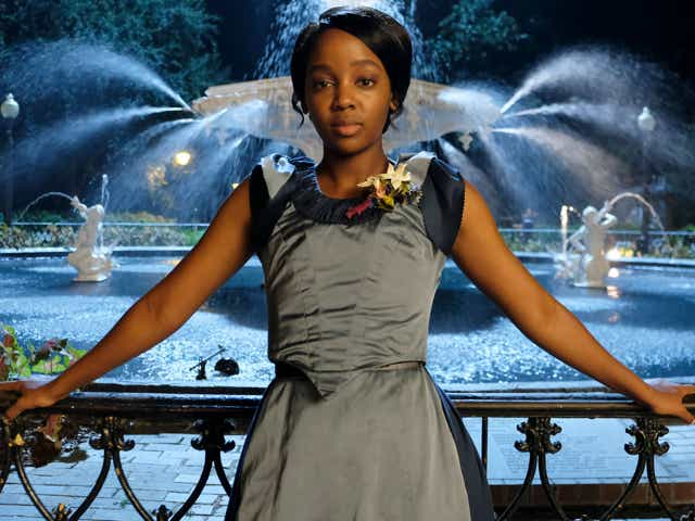 Thuso Mbedu appears in a grey dress in front of a fountain in a still from The Underground Railroad on Amazon.