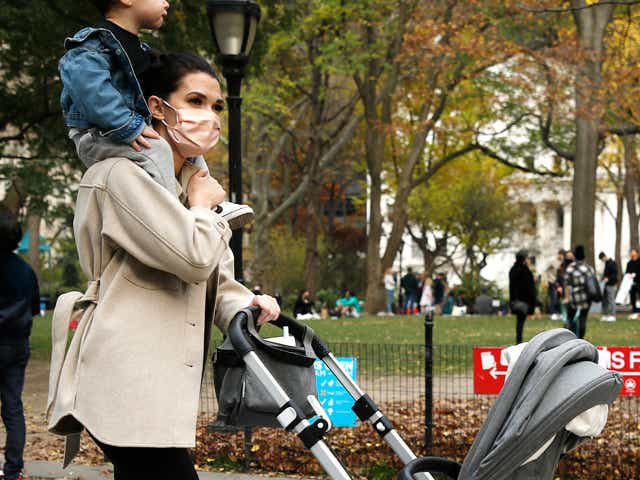 Photo of a person wearing a mask with a kid on her shoulders pushing a stroller.