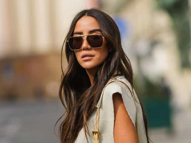 A street-style model wears aviator sunglasses and a beige linen crop top.