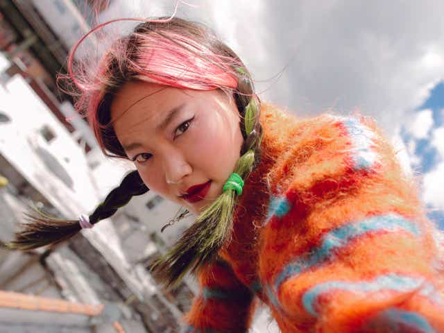 Model and creative director Gia Seo poses on a rooftop in an orange and blue striped sweater. She wears a dark red lip color and her hair is in two braids.