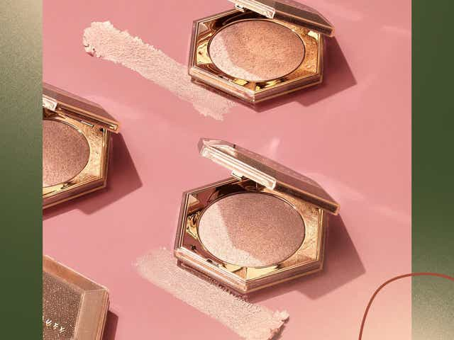 Gold highlighter compacts against a peachy pink background