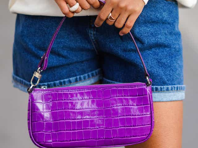 Ellie Delphine wears Asos blue denim shorts, a purple leather crocodile pattern bag from Far.
