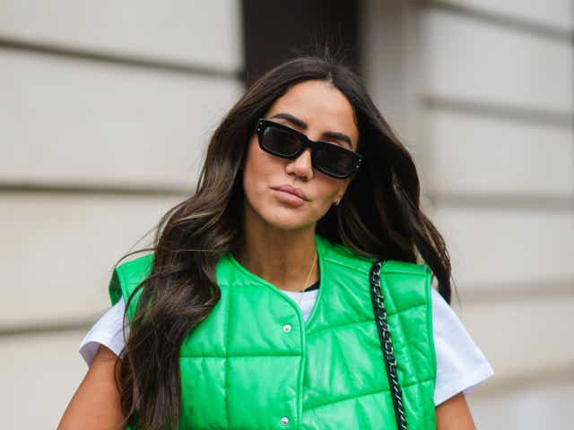 A street-style model wears a green quilted vest, a white t-shirt, and black sunglasses.