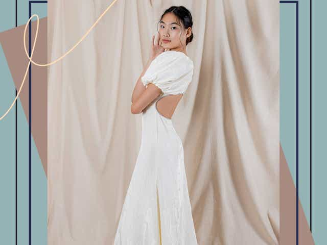 A model wearing a wedding gown with puff sleeves and open back from Katharine Polk Bridal.
