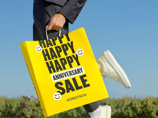 Woman holding yellow Nordstrom anniversary sale bag