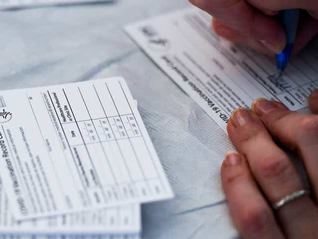 A healthcare worker fills out information on COVID-19 Vaccination Record Cards from the CDC.