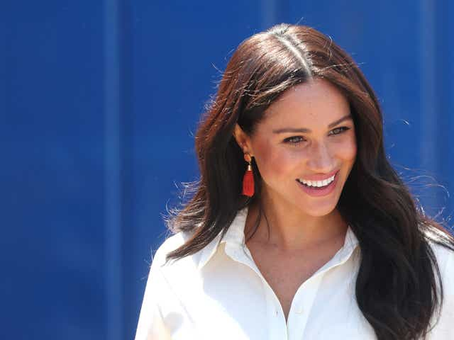 Image of Meghan, Duchess of Sussex smiling in front of a blue wall in Johannesburg, South Africa.