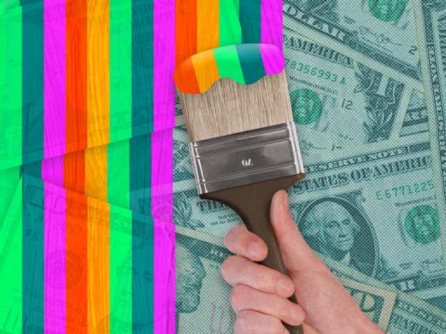 The hand of a man wearing a business suit is seen painting rainbows on top of piles of money.