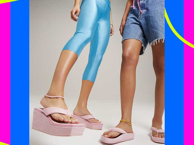 Two models wearing baby pink platform flip flops, one with denim cutoffs and another with blue spandex shorts.