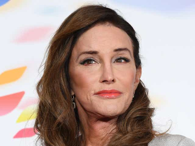 Caitlyn Jenner wearing pink lipstick and grey shirt.