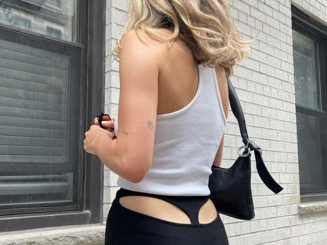 Eliza Huber wearing a white tank top with black pants that have cutouts in the back to look like a thong.