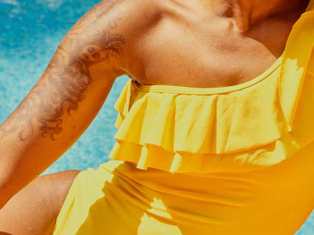 Person wearing a yellow swimsuit, reclining on their side in front of a swimming pool.