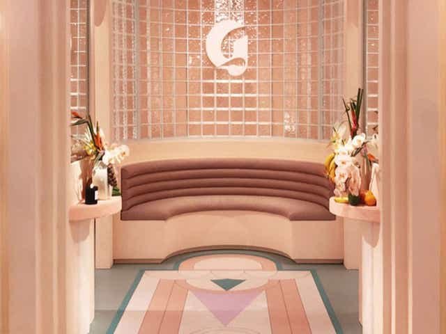 View from inside a Glossier store, a patterned pink carpet leads up to a retro semi circle pink sofa
