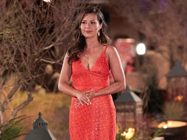 Katie stands in a red dress on The Bachelorette.