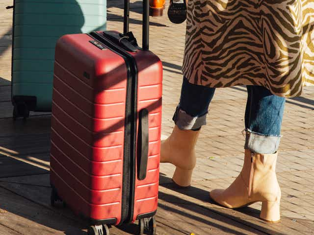 A woman in a printed coat stands with an Away suitcase