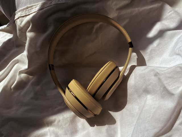Image of a pair of headphones on a white bed spread