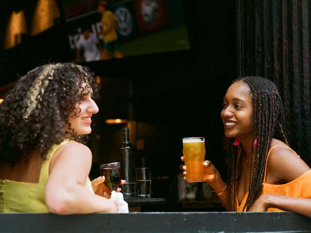 two woman share a drink on a patio without masks