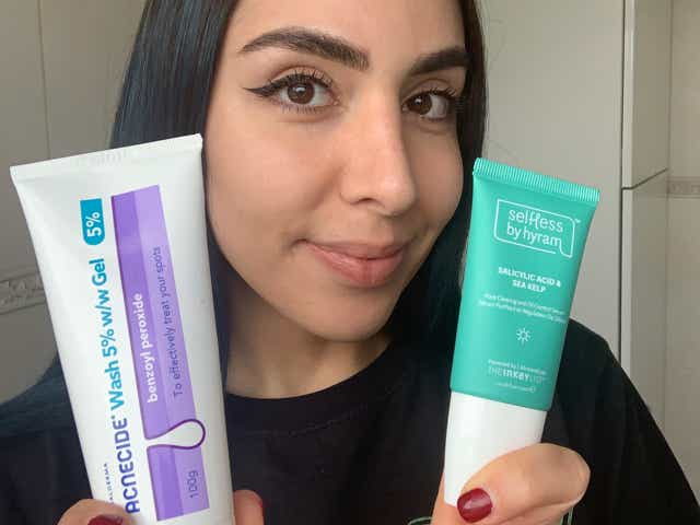 Jacqueline holding up ACNECIDE Face Wash Spot Treatment and Selfless by Hyram Salicylic Acid to camera