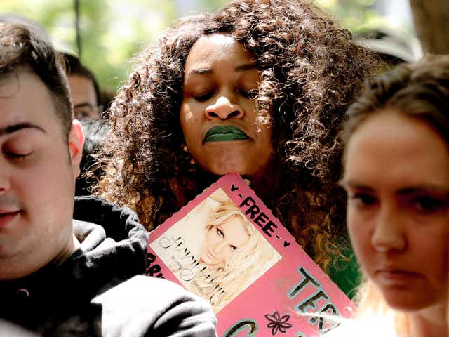 Comedian GloZell and #FreeBritney activists react to comments made by Britney Spears while listening to a feed from the courtroom during a protest at Los Angeles Grand Park during a conservatorship hearing for Spears on June 23, 2021 in Los Angeles, California. Spears is addressing the court remotely. Spears was placed in a conservatorship managed by her father, Jamie Spears, and an attorney, which controls her assets and business dealings, following her involuntary hospitalization for mental care in 2008.