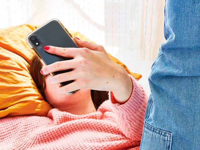 Person laying in bed with their face covered by the phone in their hand