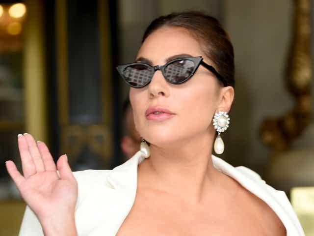 Lady Gaga wearing cat-eye sunglasses and a white dress.