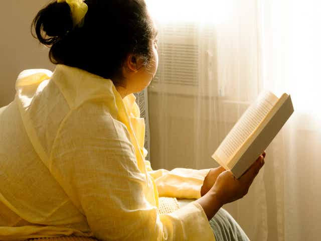 Person laying on a bed with a book in hand while looking out the window