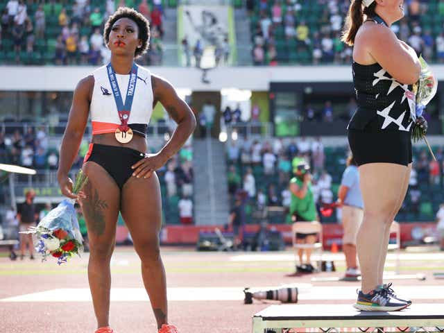 EUGENE, OREGON - JUNE 26: Gwendolyn Berry (L), third place, looks on during the playing of the national anthem with DeAnna Price (C), first place, and Brooke Andersen, second place, on the podium after the Women's Hammer Throw final on day nine of the 2020 U.S. Olympic Track & Field Team Trials at Hayward Field on June 26, 2021 in Eugene, Oregon.