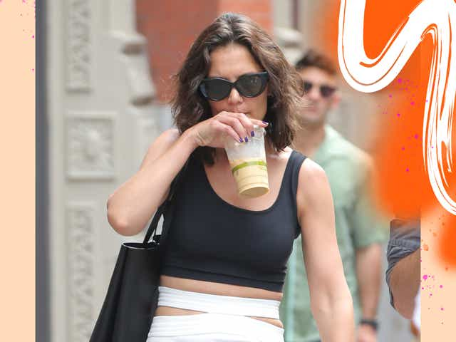 Katie Holmes in Manhattan wearing a black tank top and a cut-out white skirt.