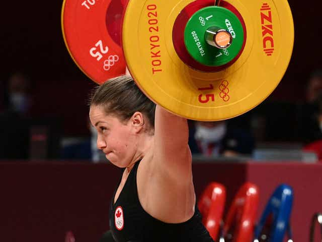 Woman holding weights over her head.