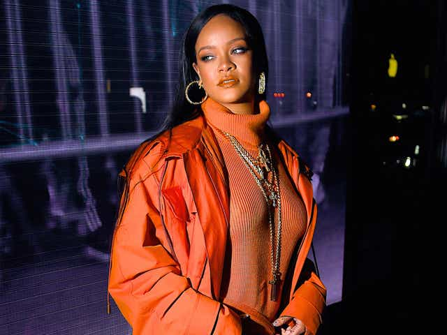 Rihanna wearing an orange turtleneck bodycon dress and parka