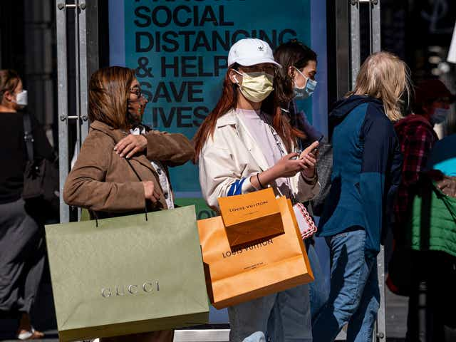 Two people with shopping bags wearing masks outside.