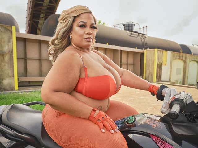 Member of Caramel Curves biker gang wearing an orange bra-panty set with matching fishnets and gloves from Savage x Fenty.