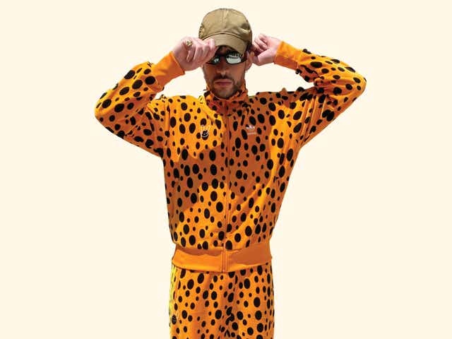 Bad Bunny wearing an orange-spotted Adidas tracksuit.
